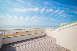a clean modern rooftop deck overlooking the beach.