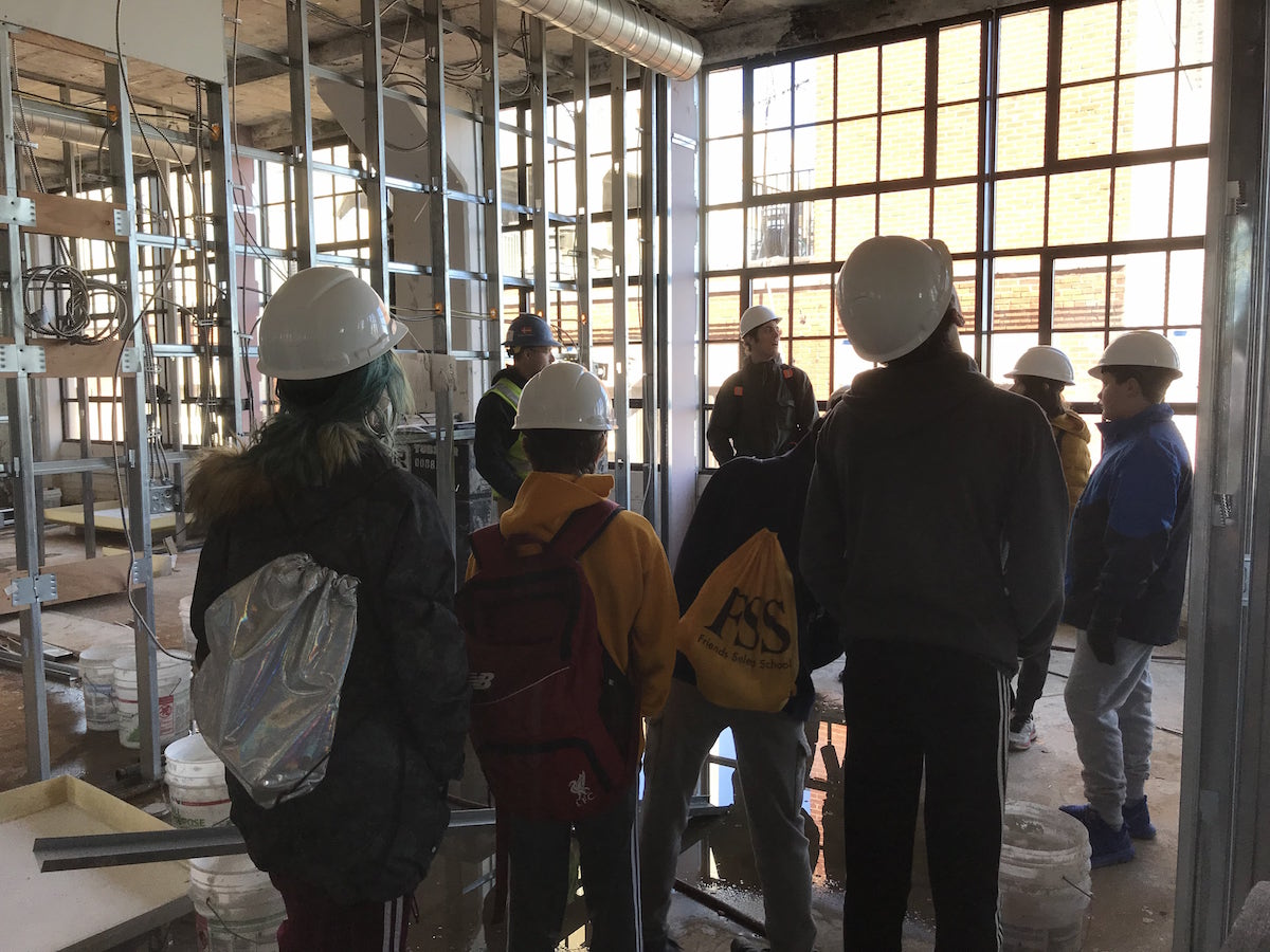 Group of young people taking a tour of a building under construction.