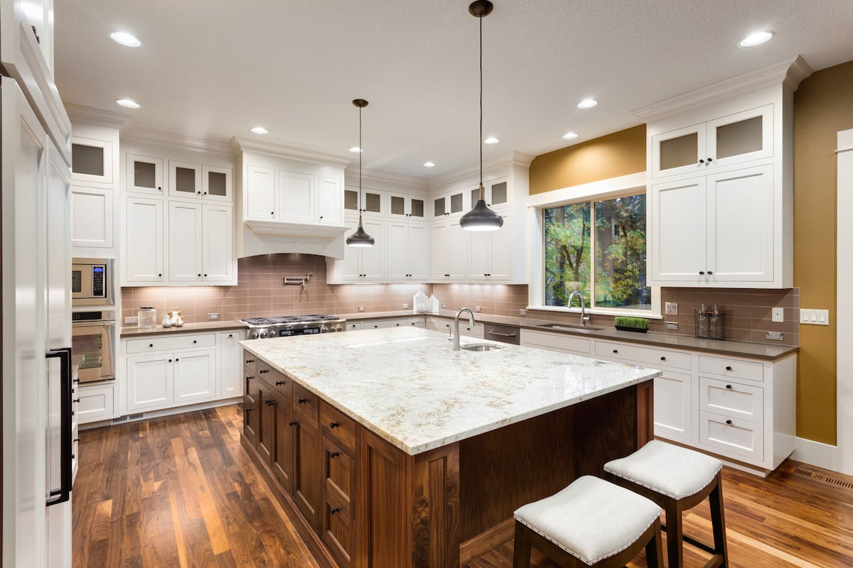 A luxury kitchen with hardwood floors and granite countertops.