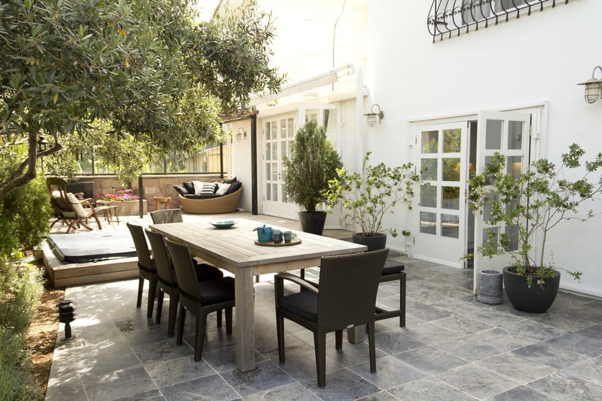 A backyard patio area with tiled floor, a space to lounge, and a dining table.