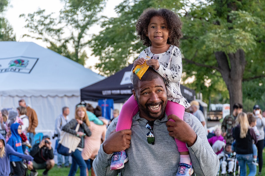 Man carrying child at fall festivals in Philly