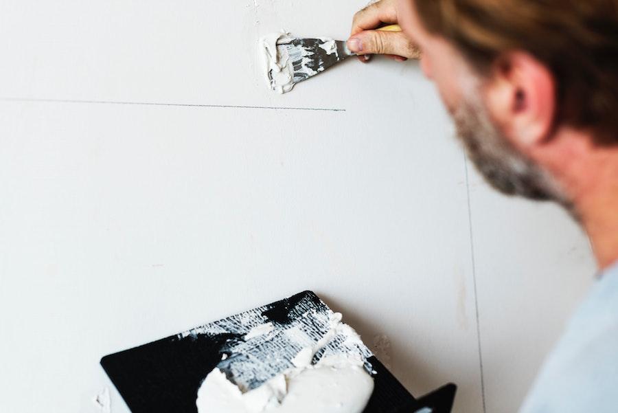 Person repairing wall